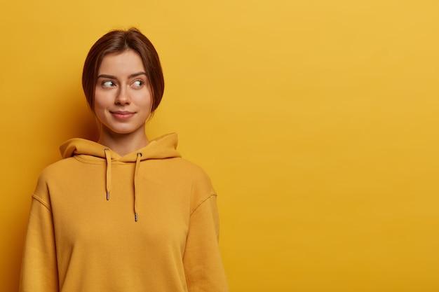 Foto de una linda adolescente que mira pensativamente a un lado, tiene el pelo oscuro peinado, usa una sudadera informal, posa contra la pared amarilla, piensa en ir de picnic con amigos el fin de semana