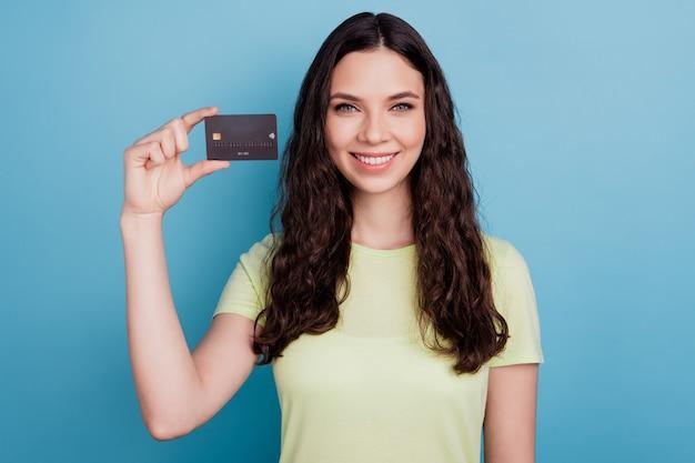 Foto de linda chica positiva demostrar tarjeta de crédito sonrisa blanca brillante sobre fondo azul.