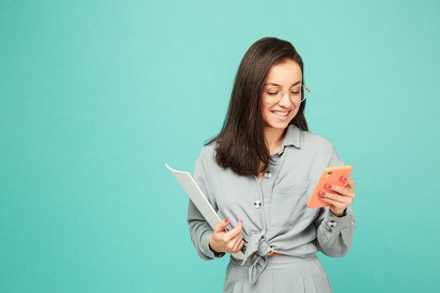 Foto de linda dama de negocios en vasos tiene papeles y mensajes de texto en el teléfono