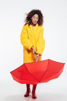 Foto de longitud completa de mujer africana sorprendida en impermeable abrir paraguas sobre fondo blanco.