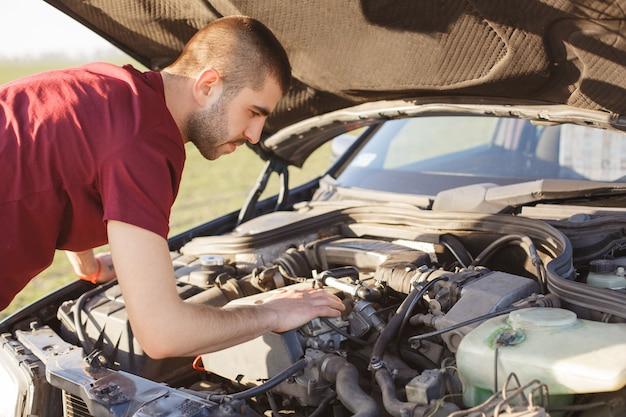 La foto del macho se para frente al capó abierto del automóvil, ha roto el vehículo en la carretera, intenta resolver el problema y reparar el daño de la máquina