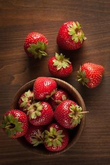 Foto macra de la fresa roja madura fresca en un tazón de fuente de madera en fondo rústico. productos naturales orgánicos.