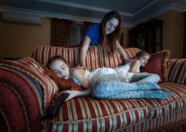 Foto de madre despertando a dos hijas que se quedaron dormidas por la noche mientras veían televisión