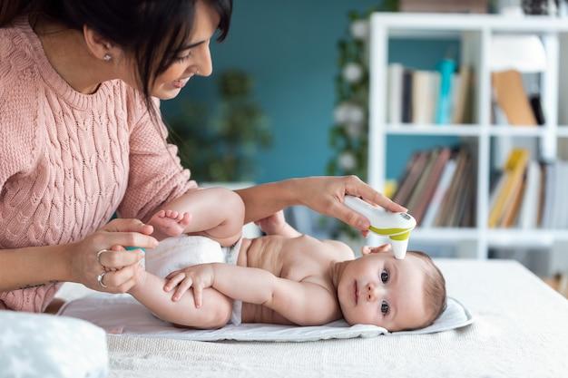 Foto de madre midiendo la temperatura de su bebé con termómetro infrarrojo en casa.