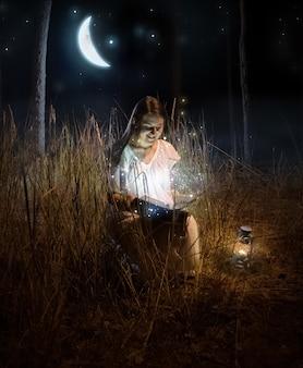 Foto mágica de hermosa mujer sentada en el bosque de noche y leyendo un libro de cuento de hadas