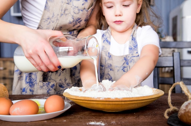 Foto de mamá e hija cocinadas juntas con harina, huevos y leche.