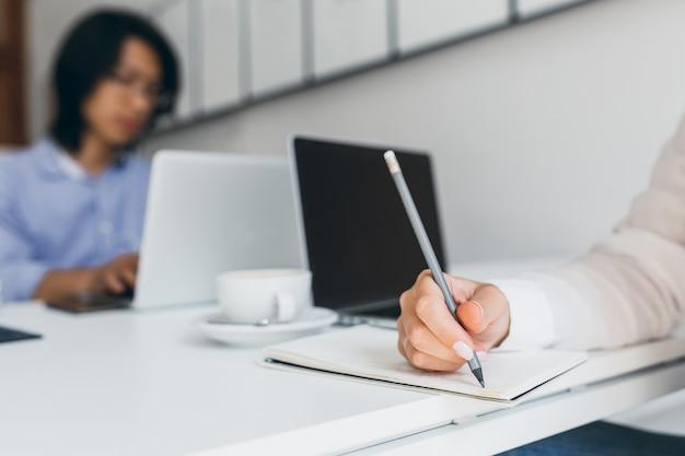 Foto de mano femenina con manicura blanca sosteniendo un lápiz con oficinista asiático