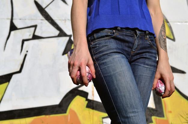 Foto de la mano de una niña con latas de pintura en aerosol en las manos sobre un fondo de pared de graffiti.