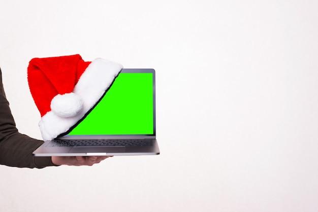 Foto de mano sujetando portátil con sombrero rojo, concepto de descuentos de vacaciones de navidad