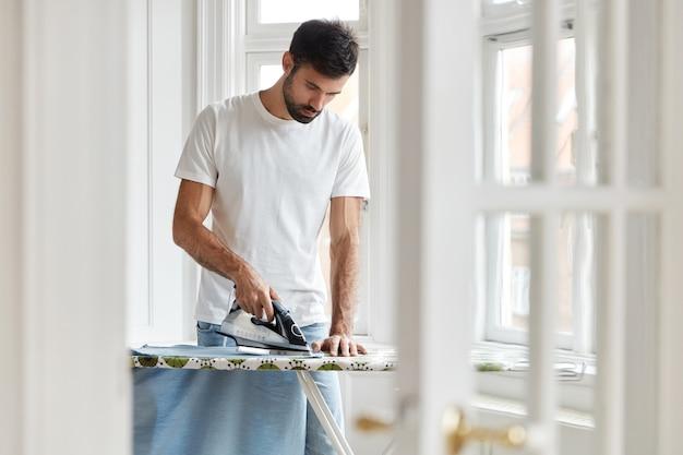 Foto de marido responsable o hombre soltero ocupado con el trabajo de la casa, plancha su camisa por la mañana en la mesa de planchado antes del trabajo