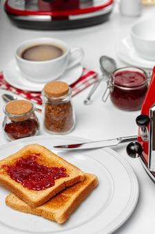 Foto de mesa de cocina con tostadas, mermeladas de frutas y cuchillo