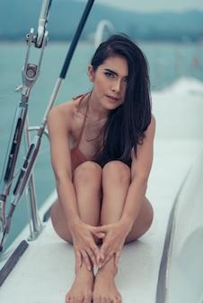 Foto de moda al aire libre de verano de una chica sexy con cabello oscuro en un lujoso bikini relajante en un yate en el mar