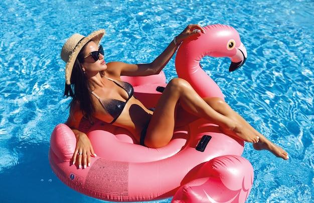 Foto de moda de hermosa chica sexy en bikini negro relajándose junto a una piscina