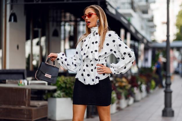 Foto de moda de hermosa modelo sexy con traje de moda. gafas de sol rojas, bolso de cuero de lujo.