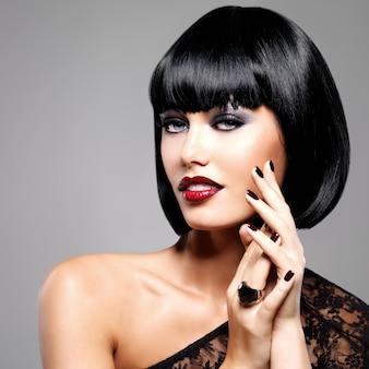 Foto de moda de una hermosa mujer morena con peinado de tiro. closeup rostro de niña con uñas y labios rojos