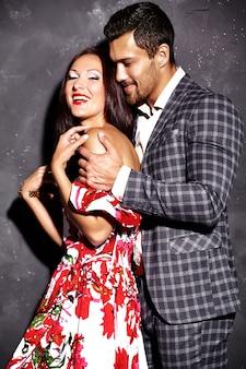 Foto de moda de hombre elegante guapo sonriente en traje con hermosa mujer sexy posando junto a la pared gris