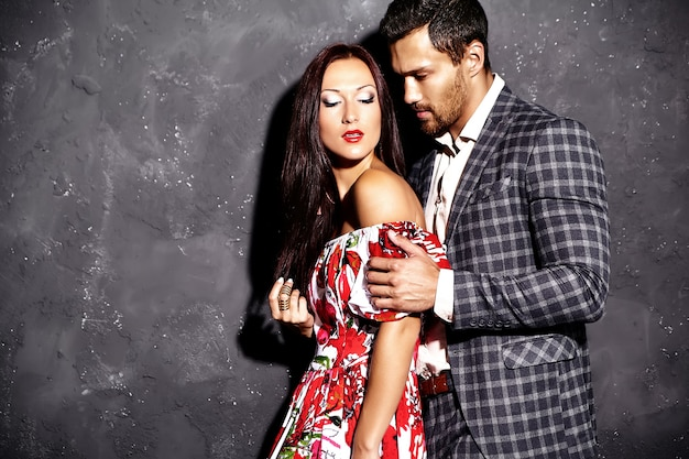 Foto de moda de hombre elegante guapo en traje con hermosa mujer sexy posando junto a la pared gris