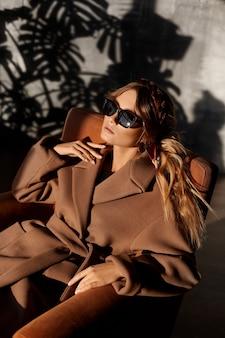Foto de moda de una joven y bella mujer con gafas de sol de moda y abrigo en un sillón en el interior. chica modelo en traje de primavera posando en el interior. estilo de vida de la ciudad. moda femenina. primer retrato
