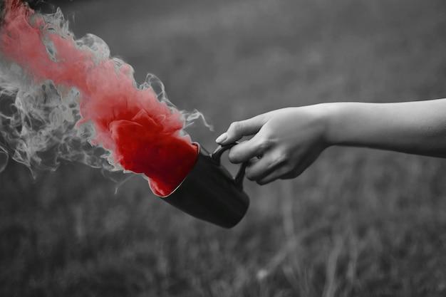 Foto de moda de mano con taza y humo rojo