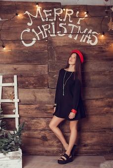 Foto de moda de mujer hermosa con el pelo oscuro en un elegante vestido negro. árbol de navidad en el fondo