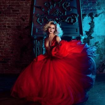 Foto de moda de mujer joven magnífica. corriendo hacia la cámara. rubia seductora en vestido rojo con falda mullida