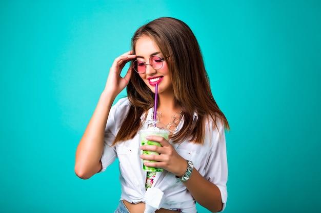 Foto de moda de primavera de estudio de niña sonriente, estilo retro hippie, bebiendo fondo de menta batido sabroso, chica hipster alegre feliz disfruta de su cóctel, estado de ánimo positivo.