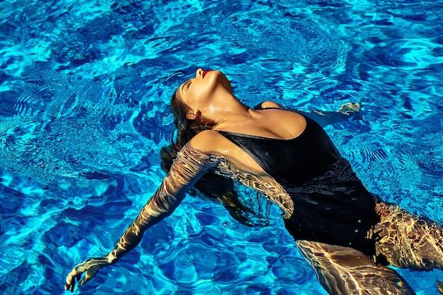 Foto de moda de sexy modelo hermosa chica caliente con cabello oscuro en traje de baño negro nadando en la espalda en la piscina con labios rojos