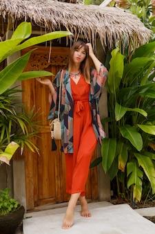 Foto de moda de verano al aire libre de mujer hermosa en traje boho posando en resort de lujo tropical.