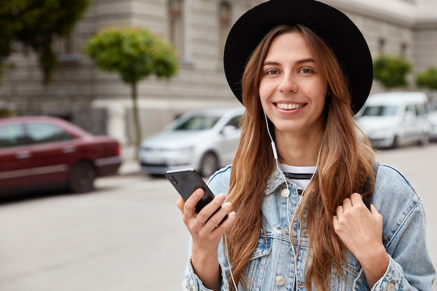 Foto de modelo femenina encantada con apariencia europea, sonríe suavemente a la cámara, escucha la canción del sitio web de radio o audiolibro