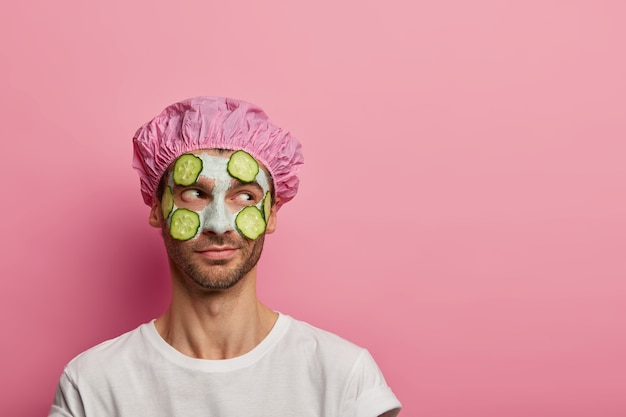 Foto de modelo masculino concentrado a un lado, tiene procedimientos de belleza, aplica mascarilla de arcilla y pepinos en la tez