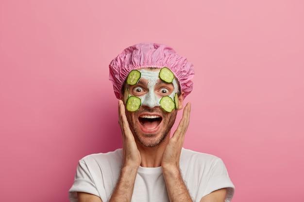 Foto de modelo masculino divertido que toca las mejillas, se ríe alegremente, disfruta de la frescura de la piel, recibe tratamientos de belleza regulares, usa mascarilla facial con rodajas de pepino