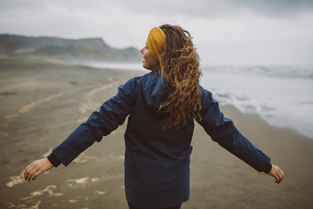 Foto de una modelo de pie en la playa con las manos abiertas expresando un sentimiento de libertad