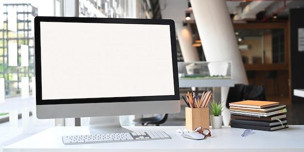 Foto de monitor de computadora de pantalla en blanco blanco, portalápices de madera, pila de libros, mouse inalámbrico y teclado que se colocan en la mesa de trabajo blanca con oficina moderna
