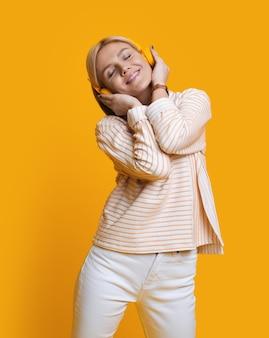 Foto monocroma de una mujer con cabello rubio escuchando música con auriculares en una pared amarilla del estudio