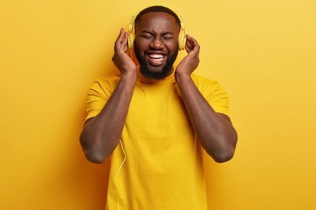 Foto monocromática de un hombre afroamericano complacido y lleno de alegría que disfruta de un sonido fuerte perfecto en auriculares nuevos, vestido con una camiseta amarilla, tiene tiempo libre, se entretiene con música. expresión feliz.