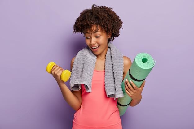 Foto de motivado saludable con peinado afro, levanta pesas, sostiene karemat, tiene una toalla sobre los hombros, vestida de manera informal