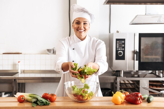Foto de mujer adulta jefe vistiendo uniforme blanco haciendo ensalada con verduras frescas, en la cocina del restaurante