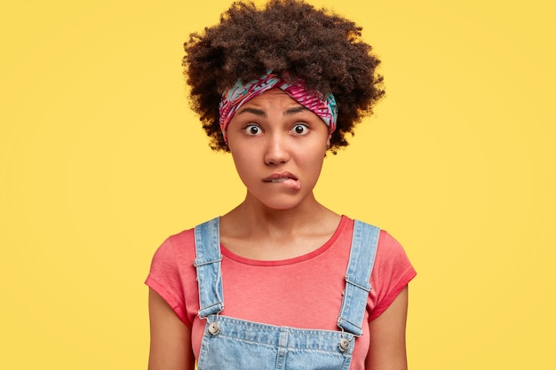 La foto de la mujer afroamericana joven hermosa nerviosa muerde los labios, se ve estresada y con perplejidad, usa overoles de mezclilla, posa sola contra la pared amarilla. concepto de reacción