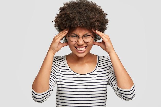 Foto de mujer afroamericana molesta aprieta los dientes, mantiene las manos en las sienes, sufre de dolor de cabeza, viste un suéter a rayas casual, aislado sobre una pared blanca. concepto de sentimiento negativo