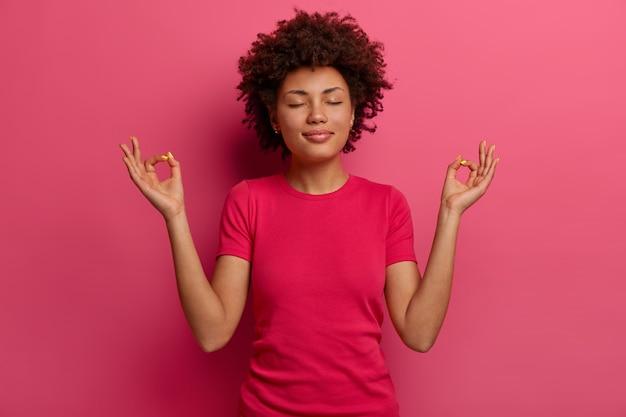 La foto de una mujer afroamericana relajada muestra un signo zen o bien, medita en el interior, tiene una expresión tranquila, cierra los ojos, usa una camiseta informal, mantiene la paciencia, practica ejercicios de yoga, posa en el interior