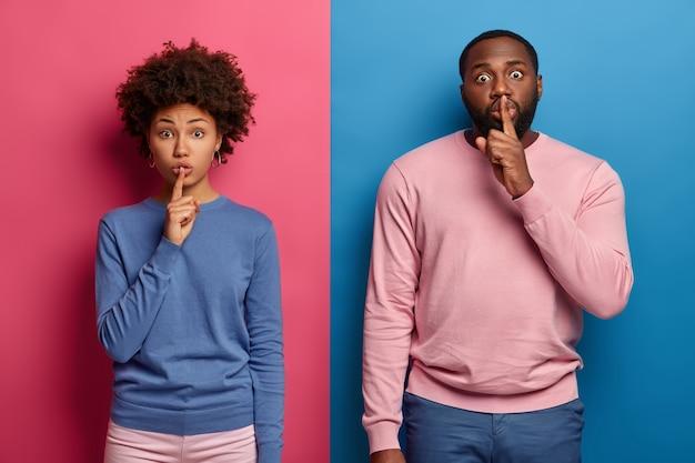 Foto de una mujer afroamericana sorprendida y un hombre presionando los dedos índices en los labios, pide silencio y silencio, le cuenta un secreto a alguien