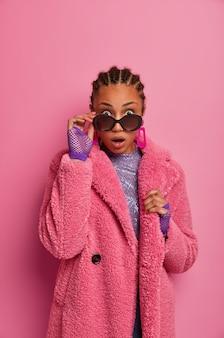 Foto de una mujer afroamericana sorprendida que se ve con gafas de sol con expresión de asombro, no puede creer lo que ve, viste abrigo de invierno y guantes deportivos, aturdida por grandes descuentos en el centro comercial