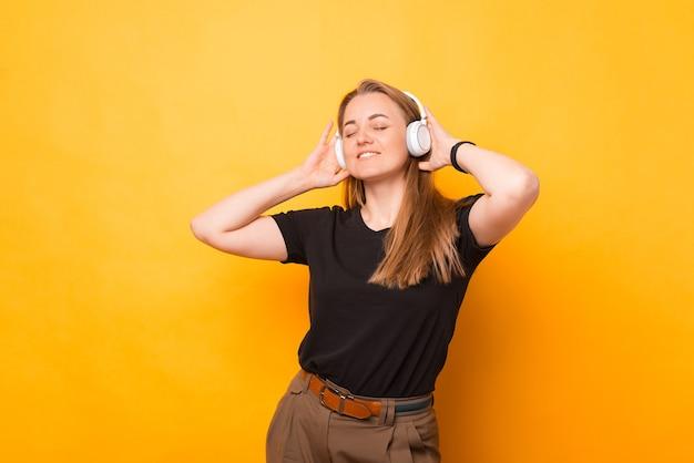 Foto de mujer alegre escuchando música en auriculares inalámbricos blancos sobre fondo amarillo