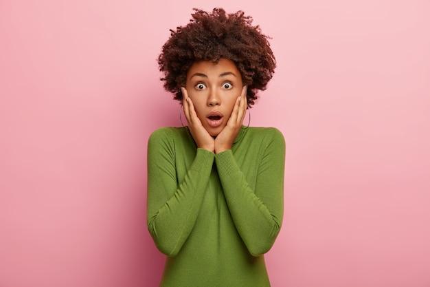 Foto de mujer angustiada en pánico toca las mejillas, mira con ansiedad, viste poloneck verde, mira nerviosamente a la cámara, aislada sobre fondo rosa
