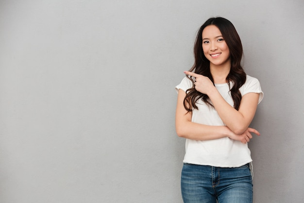 Foto de mujer asiática afable en camiseta casual y jeans posando en cámara y apuntando con el dedo a un lado en copyspace, aislado sobre la pared gris