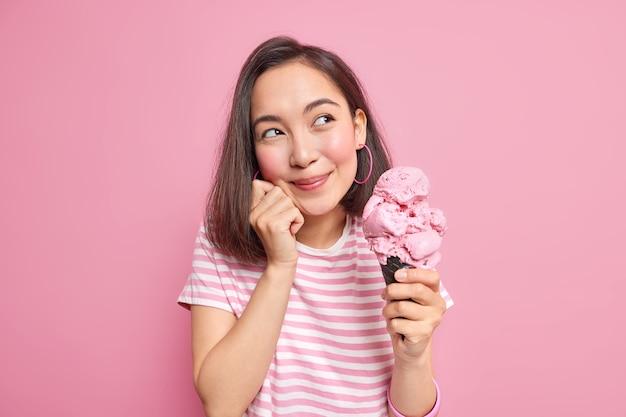 Foto de mujer asiática bonita que se ve soñadora a un lado recuerda agradables recuerdos come sabroso postre de verano sostiene un gran cono de helado vestida con modelos casuales de camiseta
