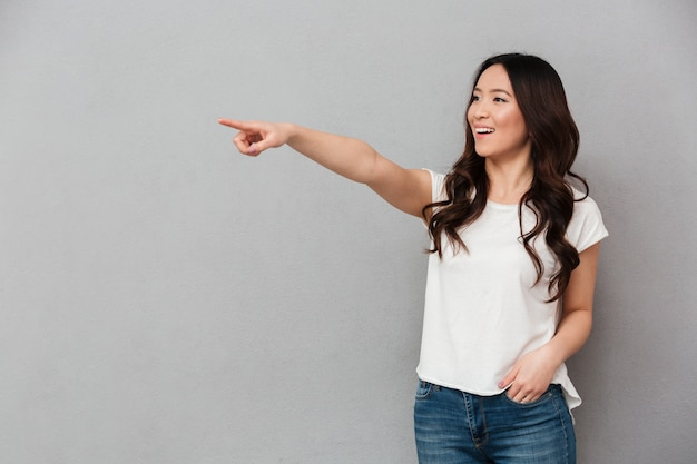 Foto de mujer asiática satisfecha en camiseta casual y jeans posando en cámara y apuntando con el dedo a un lado en copyspace, aislado sobre la pared gris