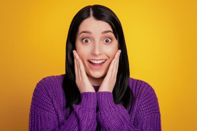 Foto de mujer asombrada mira buenas noticias increíbles impresionado toque manos mejillas usan suéter aislado sobre fondo de color brillante