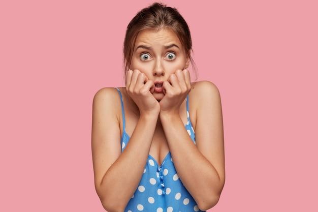 Foto de mujer asustada mantiene las manos cerca de la boca
