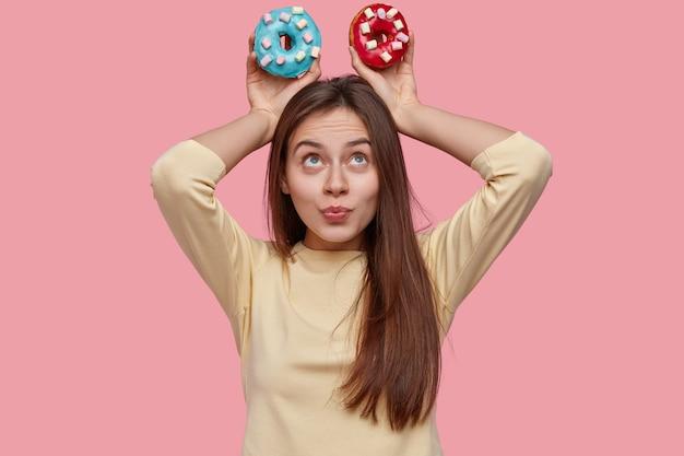 Foto de mujer atractiva con cabello oscuro, mantiene coloridos donuts sobre la cabeza, demuestra comida chatarra